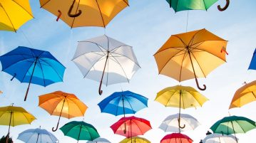 Assorted colors of umbrella hanging on black wire